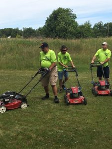 Green Grass Guys mowing a large lawn