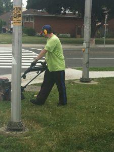 Green Grass Guys team member mowing grass