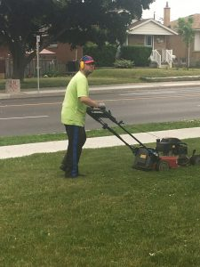 Green Grass Guys team member mowing the lawn