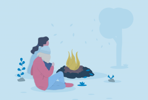 two teens outside sitting by a campfire