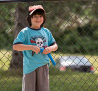 little boy with a baseball hat on, playing outside
