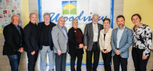 group standing in front of Woodview logo and smiling into the camera