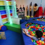 young boy plays in ball pit inside sensory room