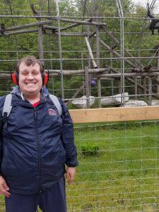 smiling man next to monkey cage at zoo