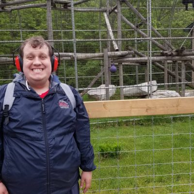 smiling man next to monkey cage at zoo