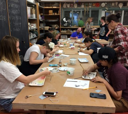 youth painting ceramic plates