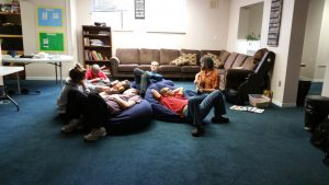 music teacher playing to youth relaxing on bean bags