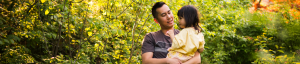 Young dad holding daughter and smiling in the garden
