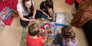 counsellor and children playing boardgame