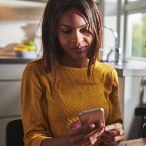 woman checking phone in her kitchen