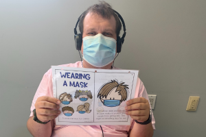 adult client wearing headphones and face mask