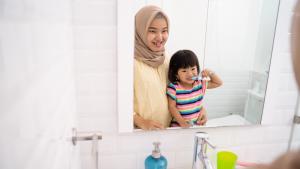 Mother teaching child to brush teeth